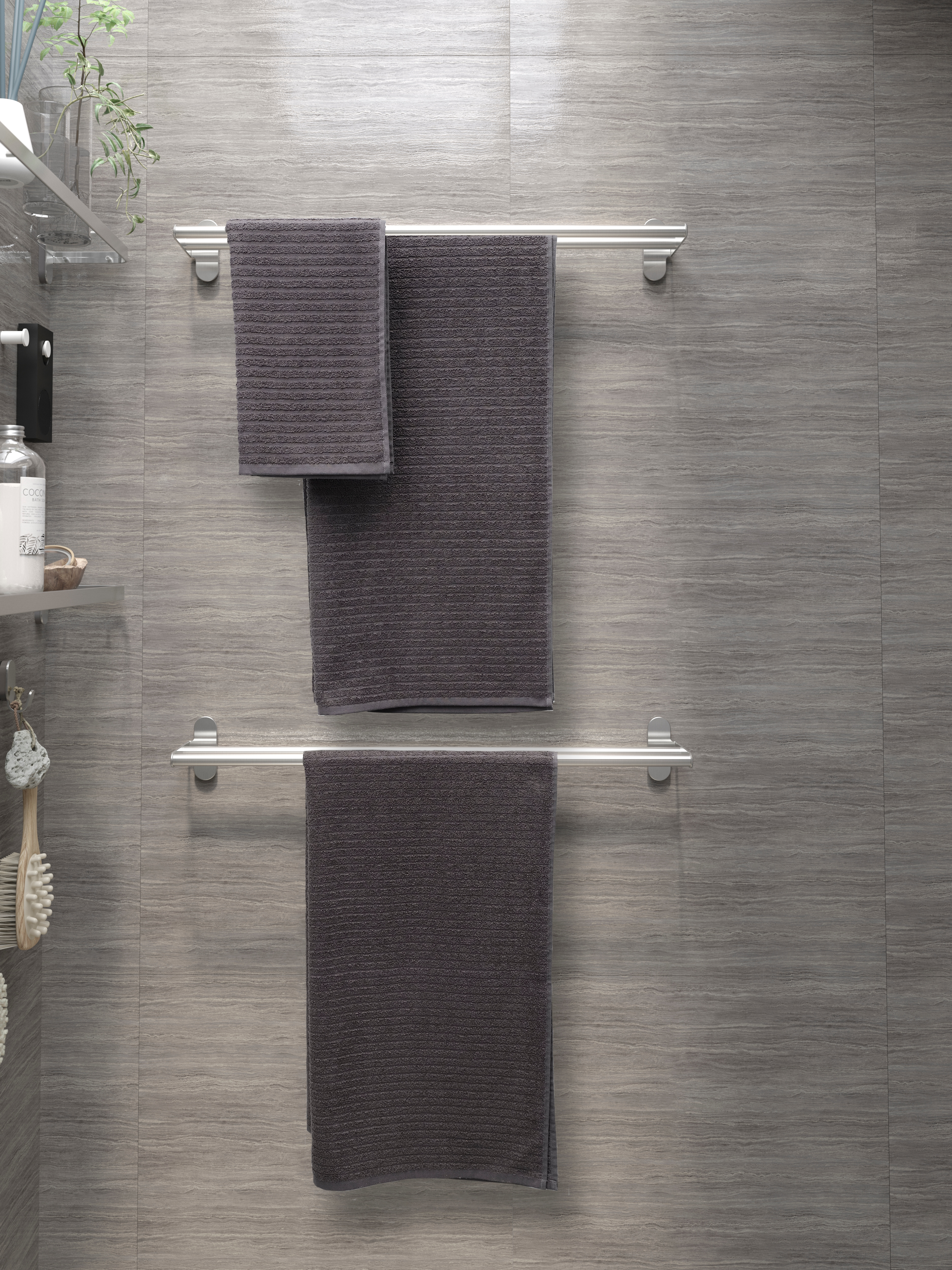 Bathroom with textured tiles, towel rails, hand and bath towels, glass shelf, hooks, clear vase, toiletries, shower brush.