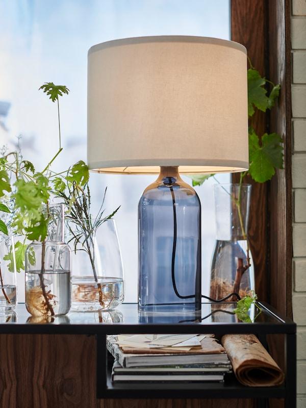 Szürke FÖRENLIG váza, átlátszó BERÄKNA váza és TONVIS asztali lámpa egy üvegasztalon.