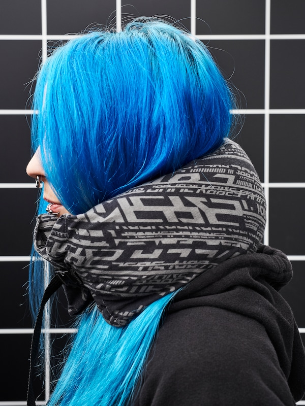 Close-up of a woman in profile. She has bright blue hair and a black hoodie and wears a LÅNESPELARE neck pillow.