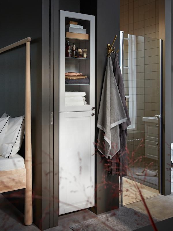 Kabinet tinggi GODMORGON berwarna kelabu cerah dengan pintu kaca yang terapat tuala, kotak storan dan produk pencukur di dalamnya.