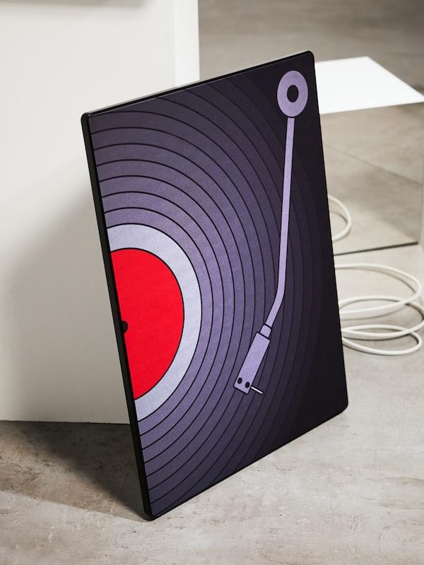 Gros plan d'un cache-enceinte SYMFONISK pour cadre avec enceinte arborant l'image d'un tourne-disque en violet foncé et rouge, posé sur le sol.