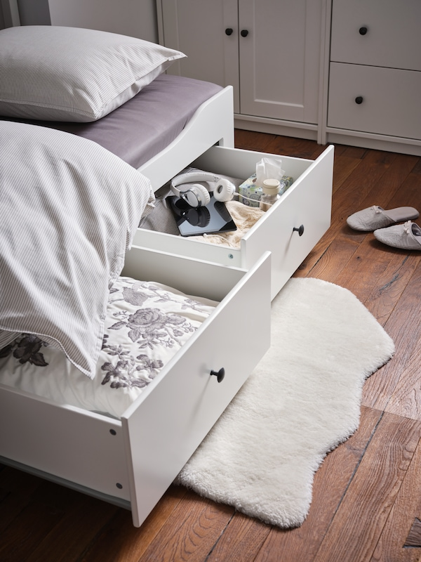 A white TOFTLUND rug lies on the floor underneath two open drawers of a HEMNES day-bed with 3 drawers/2 mattresses.