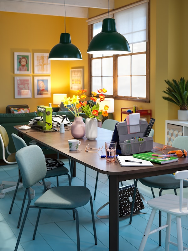 A brown STRANDTORP extendable table with accessories for paperwork and sewing on it, and flowers in a pair of vases.