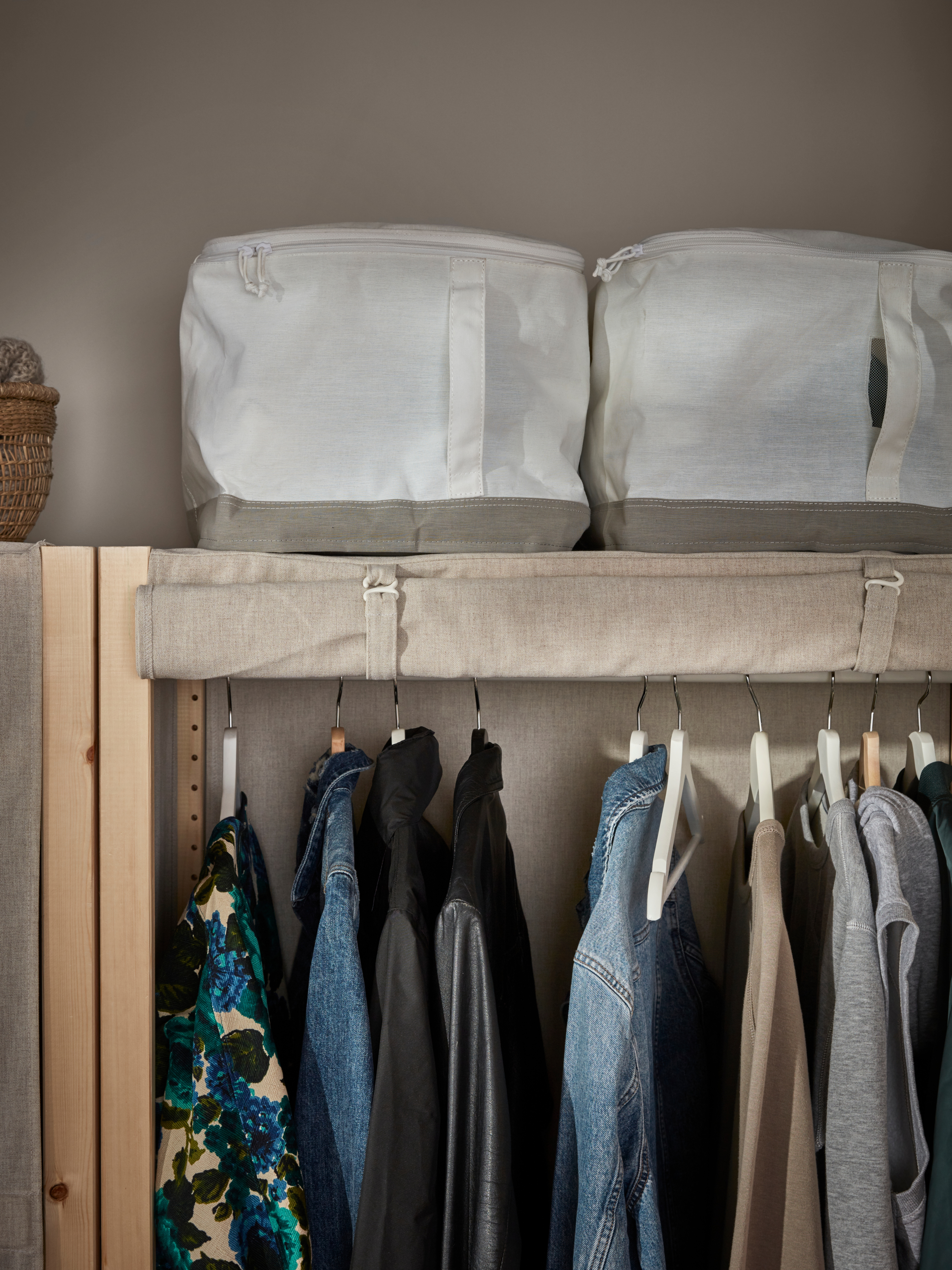 Two polyester LACKISAR storage cases on top of a shelving unit in pine with a rolled up cover and coats hanging on a rail.