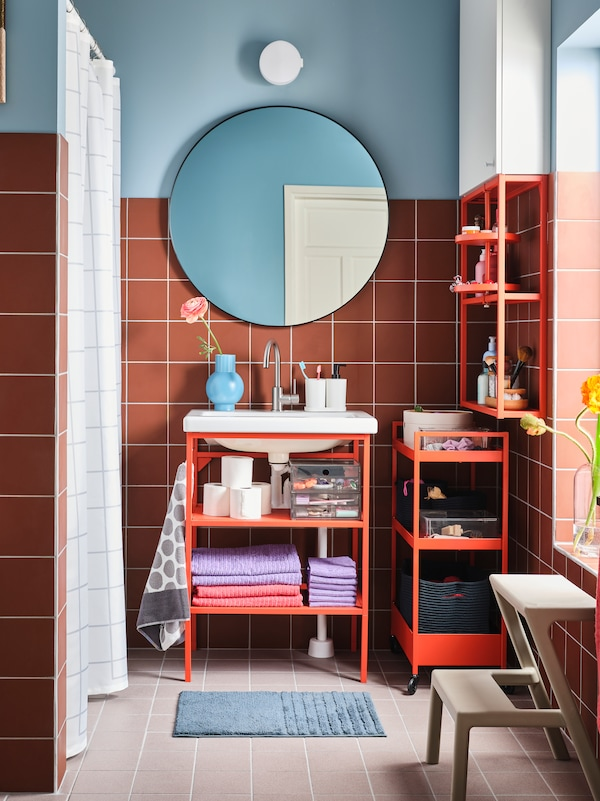 A colourful bathroom with a red-orange ENHET wash-stand below a round mirror, next to more ENHET open storage.