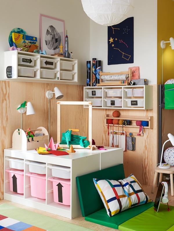 O cameră de copil cu un sistem de perete combinat TROFAST în care se află cutii de depozitare alb și roz cu jucării și alte obiecte deasupra.