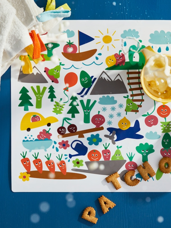 Milk is being splashed from a mug on a colourful MATVRÅ place mat on which some biscuits and KRAMA washcloths are lying.