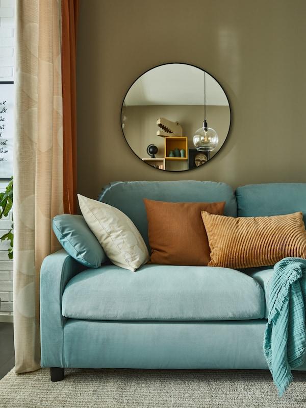 모스그린 색상의 벽에 등받이가 높은 푹신한 블루그린 소파가 있고 커다란 원형 거울과 황토색 쿠션이 있어요.