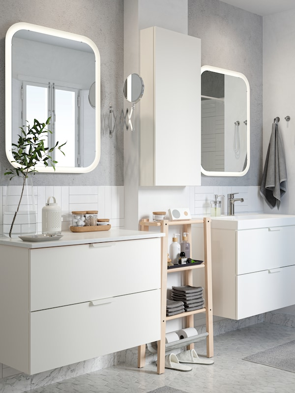 A white/gray bathroom with two white sink cabinets and 2 white mirrors.
