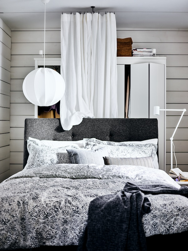 A dark gray IDANÄS upholstered bed with a wardrobe and a white curtain behind it and a NYMÅNE reading lamp beside it.