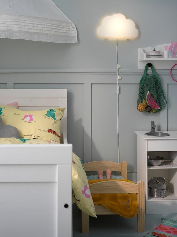 Aplica LED UPPLYST montată pe perete are formă de nor și răspândește o lumină caldă în apropierea patului alb pentru copii.