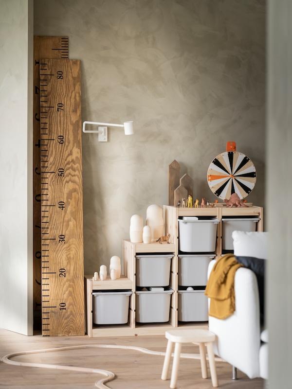 Ein Kinderzimmer mit TROFAST Aufbewahrung in Birke mit weissen Boxen und Spielzeug am Boden.