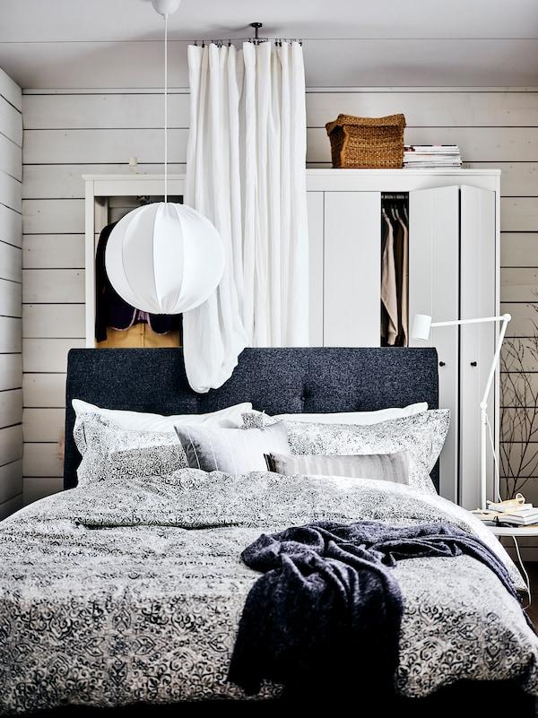 Ein dunkelgraues IDANÄS Polsterbett mit der ÄNGSKLOCKA Bettwäsche vor einer weissen Gardine und zwei Kleiderschränken.