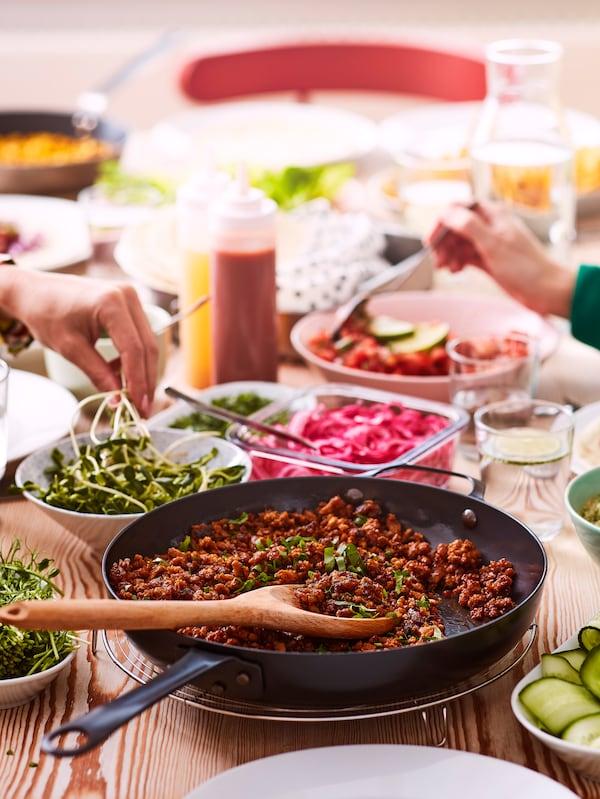 """Ustawiona na drewnianym stole patelnia z roślinnym """"mięsem"""" mielonym VÄRLDSKLOK i świeżymi ziołami, otoczona miseczkami z przyprawami."""