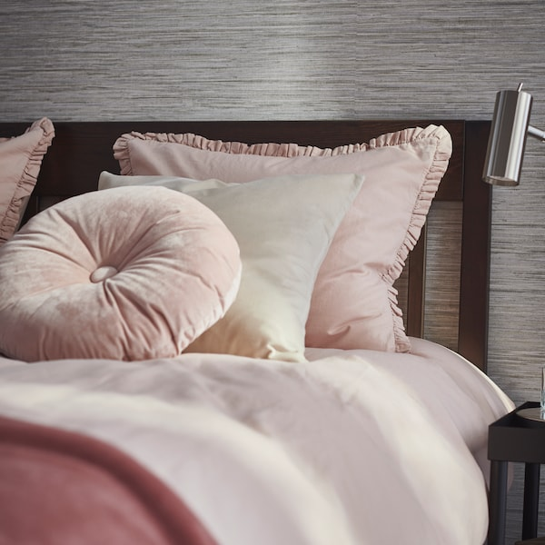 A light pink KRANSBORRE cushion lies on a dark brown stained IDANÄS bed with light pink KRANSKRAGE bed linen.