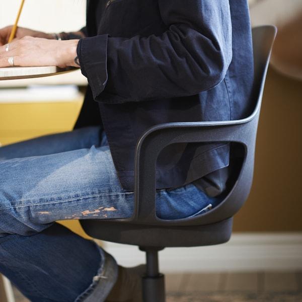 Eine Person mit einem blauem Hemd und Jeans sitzt auf einem ODGER Drehstuhl in Anthrazit an einem Tisch.