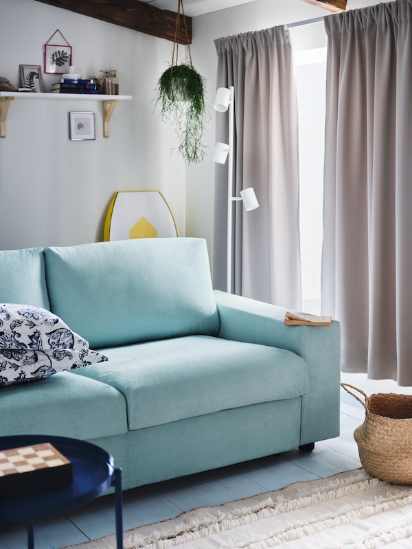 A light blue VIMLE two-seat sofa-bed with wide armrests in a summer house with windows dressed with room darkening curtains.