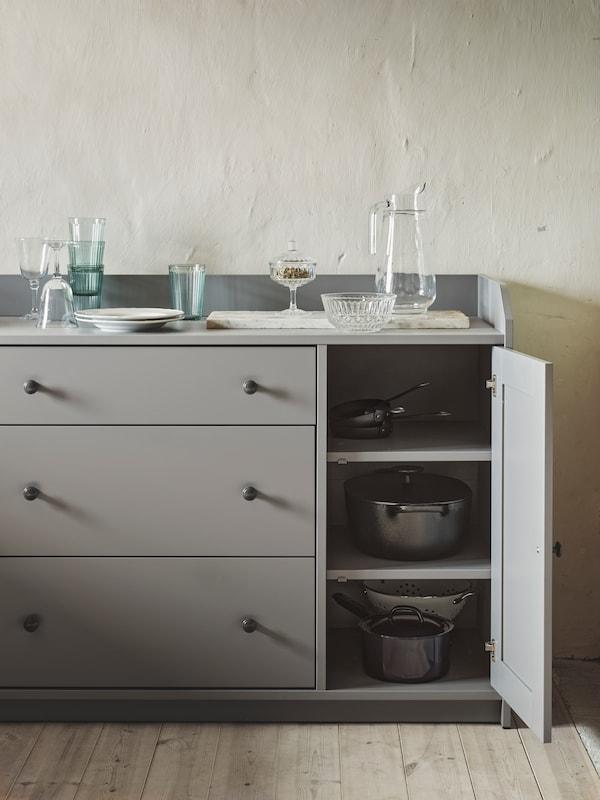 Ein graues HAUGA Sideboard mit drei Schubladen und zwei Türen. Eine Tür steht offen; im Schrank ist Geschirr zu sehen. Darauf stehen Gläser und Geschirr.