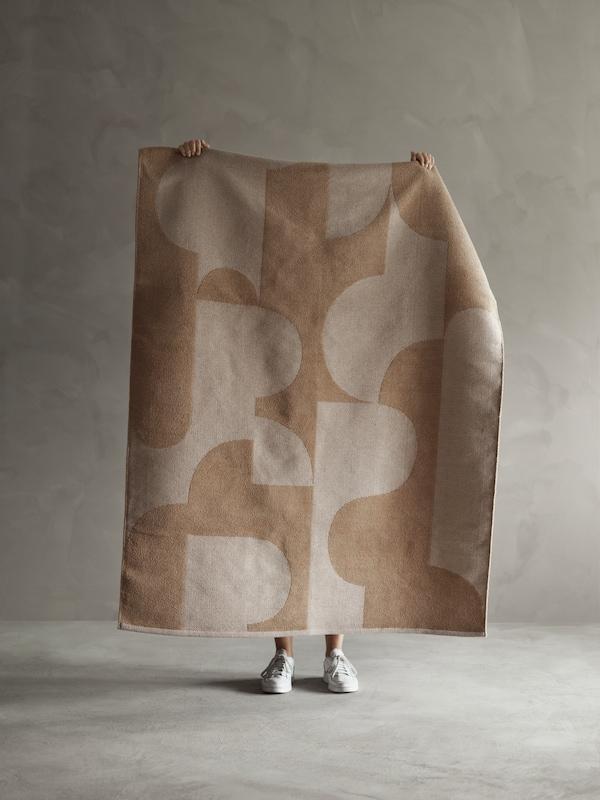 En person holder et RÖDASK tæppe op, så det markante, abstrakte print og jacquard-vævningen er synlig.
