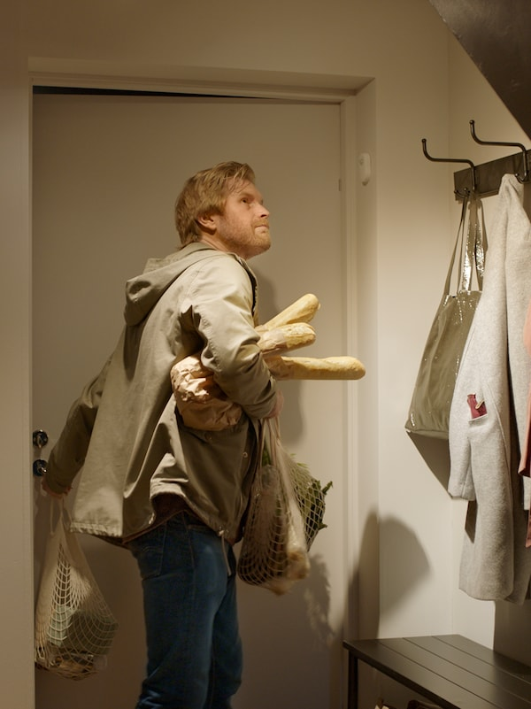 A man entering a home, carrying bread and diverse groceries in his arms, with clothes and a bag hanging from a rack.