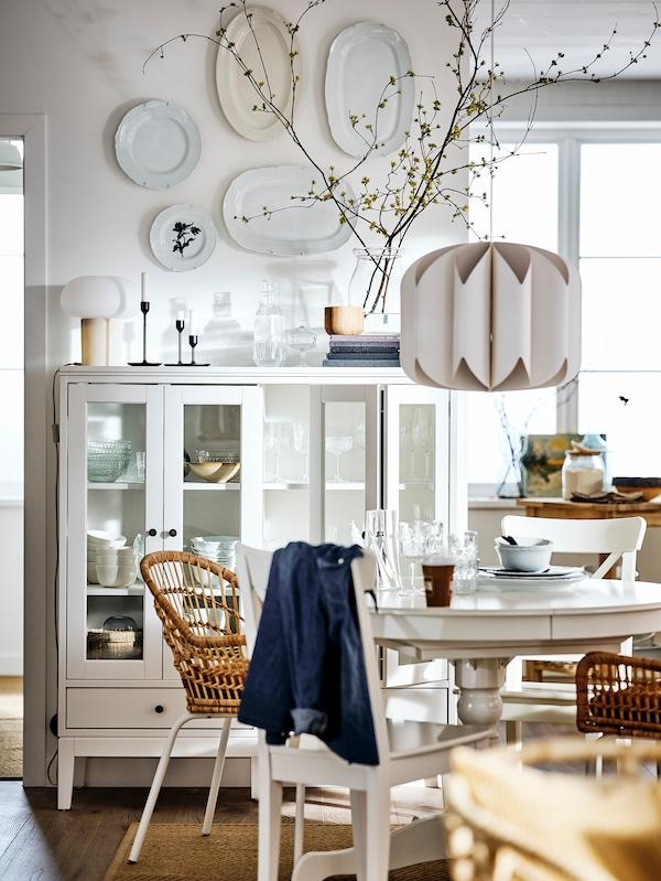 Une salle à manger blanche meublée d'une vitrine IDANÄS et d'une table INGATORP entourée de chaises blanches et en rotin.