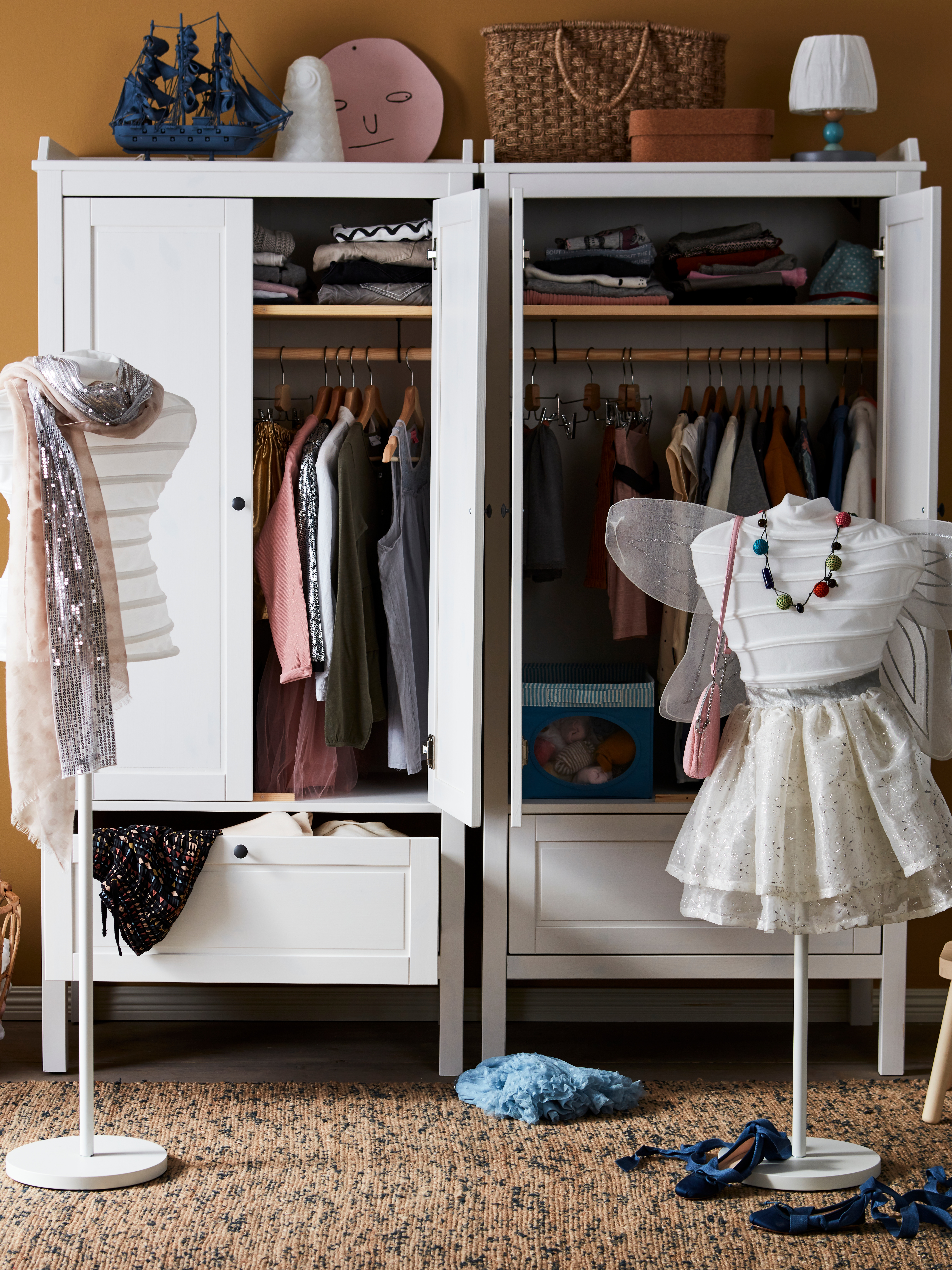 Two partly dressed, torso-shaped clothes stands are in front of two, white SUNDVIK wardrobes filled with clothes.