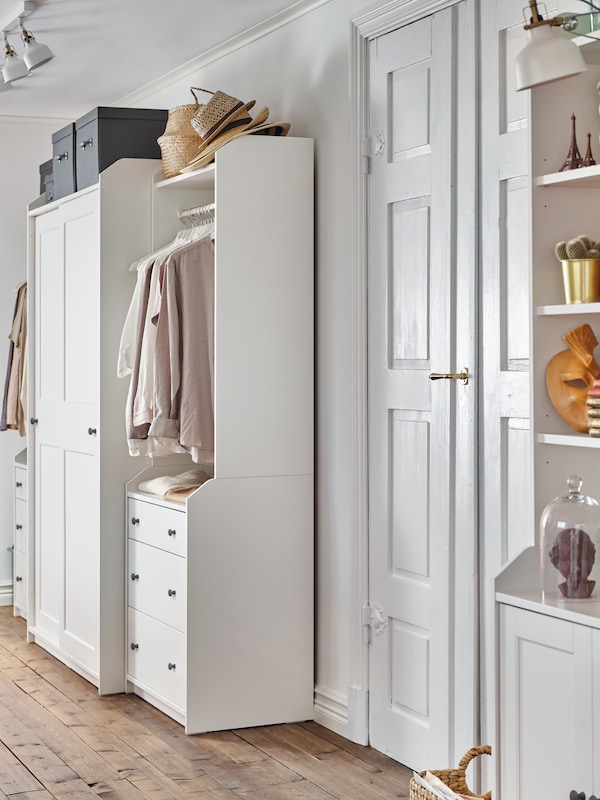 A high cabinet, a closed wardrobe and two open wardrobes from the HAUGA series create a matching look through two rooms.