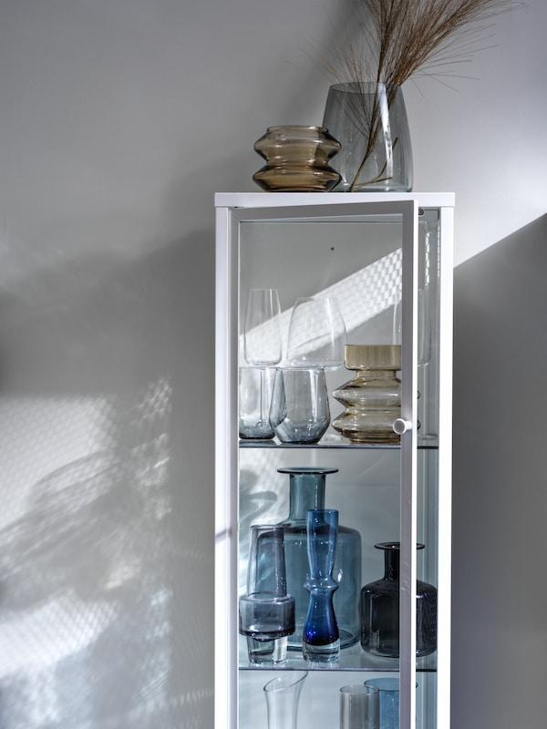 Distintos tipos de floreiros e vasos de cristal expostos nun armario BAGGEBO con portas de vidro abertas.