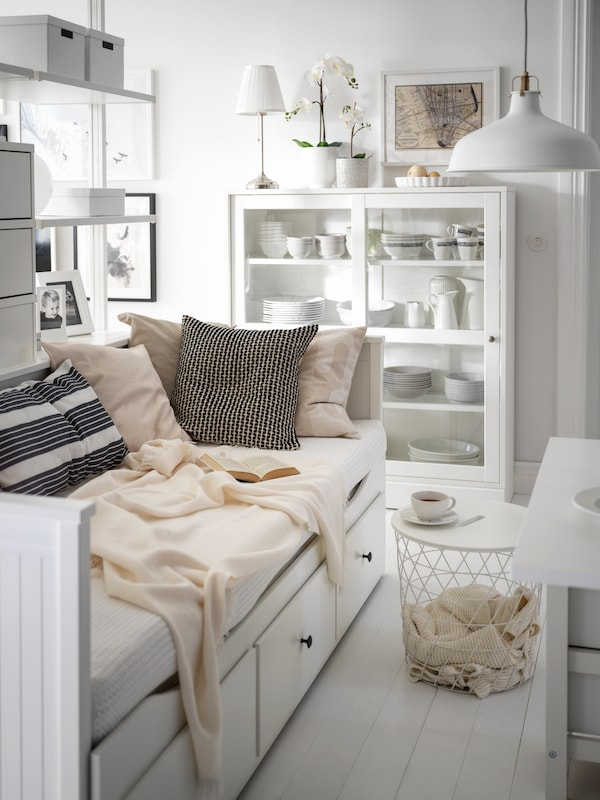A white HEMNES day-bed laden with cushions and textiles, a white KVISTBRO storage table beside it, in a light living room.