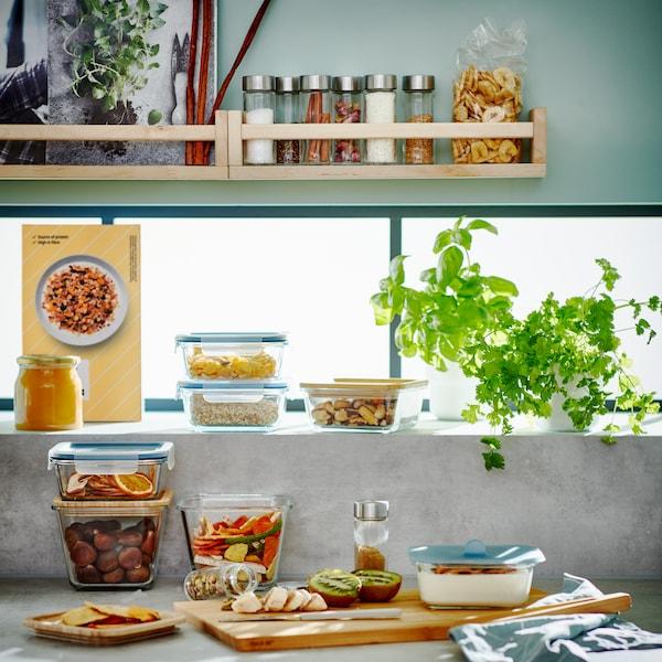 Un comptoir de cuisine avec des contenants alimentaires empilés en verre et une planche à découper en bambou recouverte de kiwis et de bananes coupés.