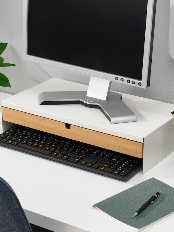 A monitor stand on a desk with a monitor on top.