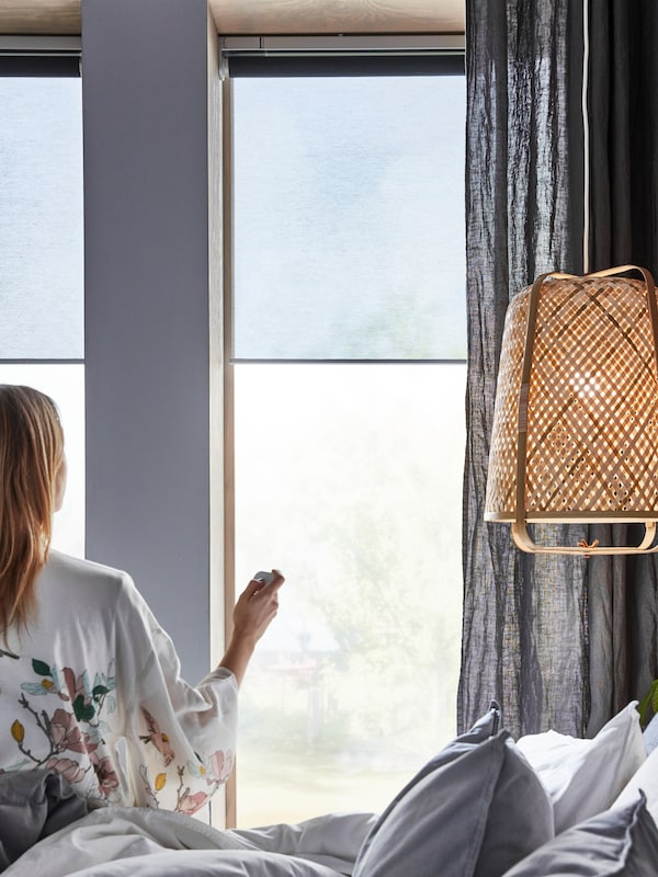 A woman, on a bed near a KNIXHULT pendant lamp, uses a remote control on KADRILJ roller blinds hanging in the windows.