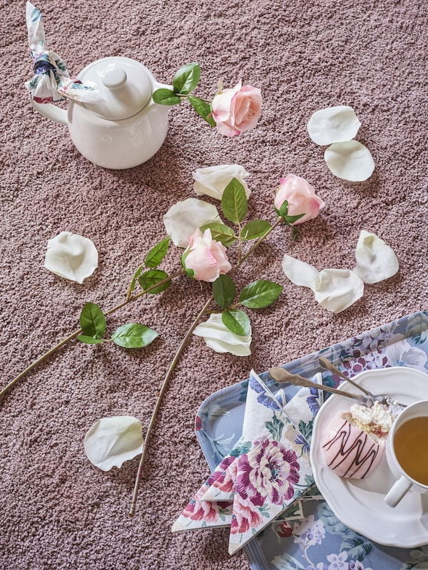 Pink and white flowers and petals lying on the floor next to a tray and teapot on a pink rug.