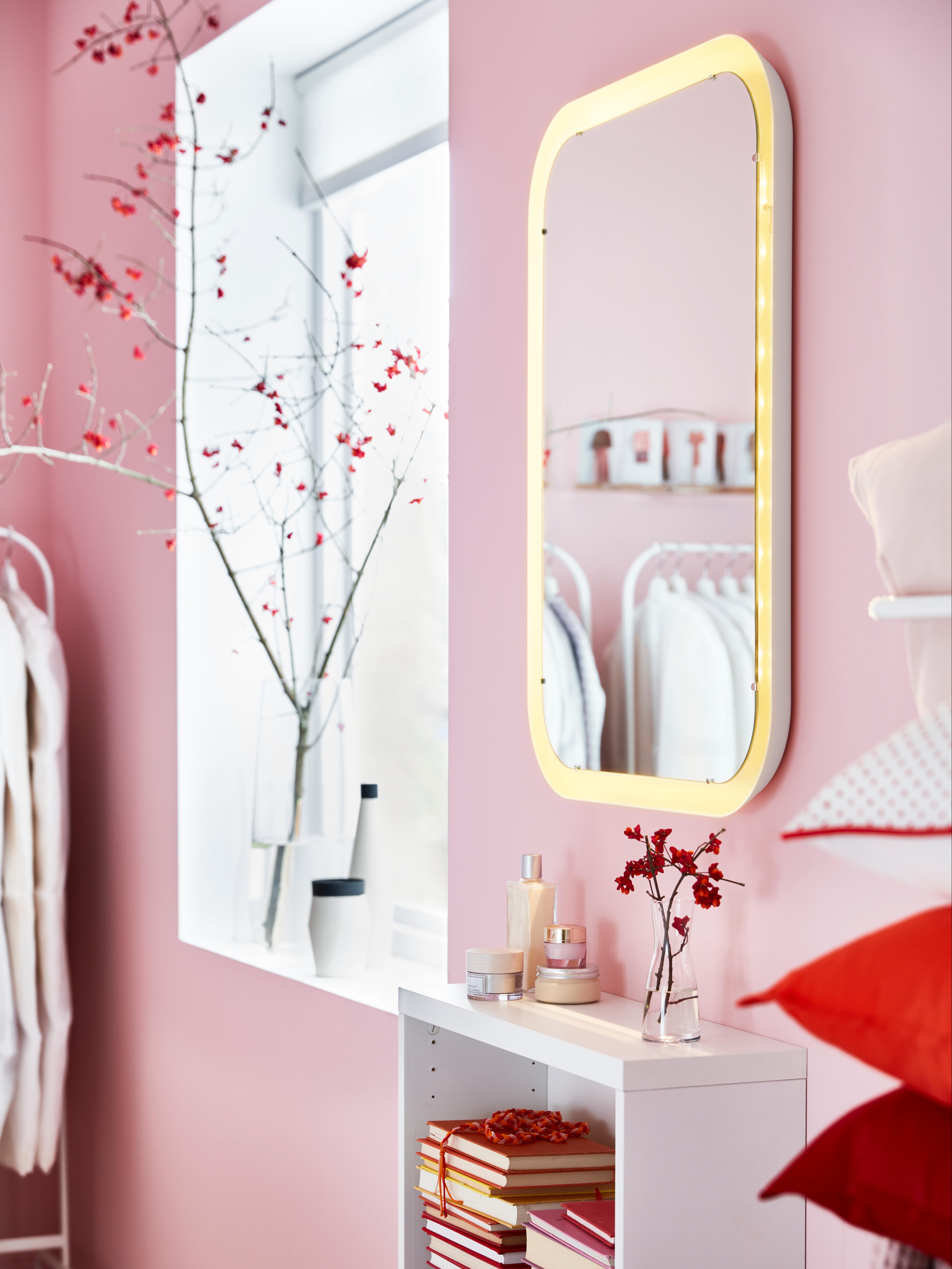 Specchio rettangolare STORJORM bianco con illuminazione integrata e angoli arrotondati, montato verticalmente sopra un pensile a giorno.
