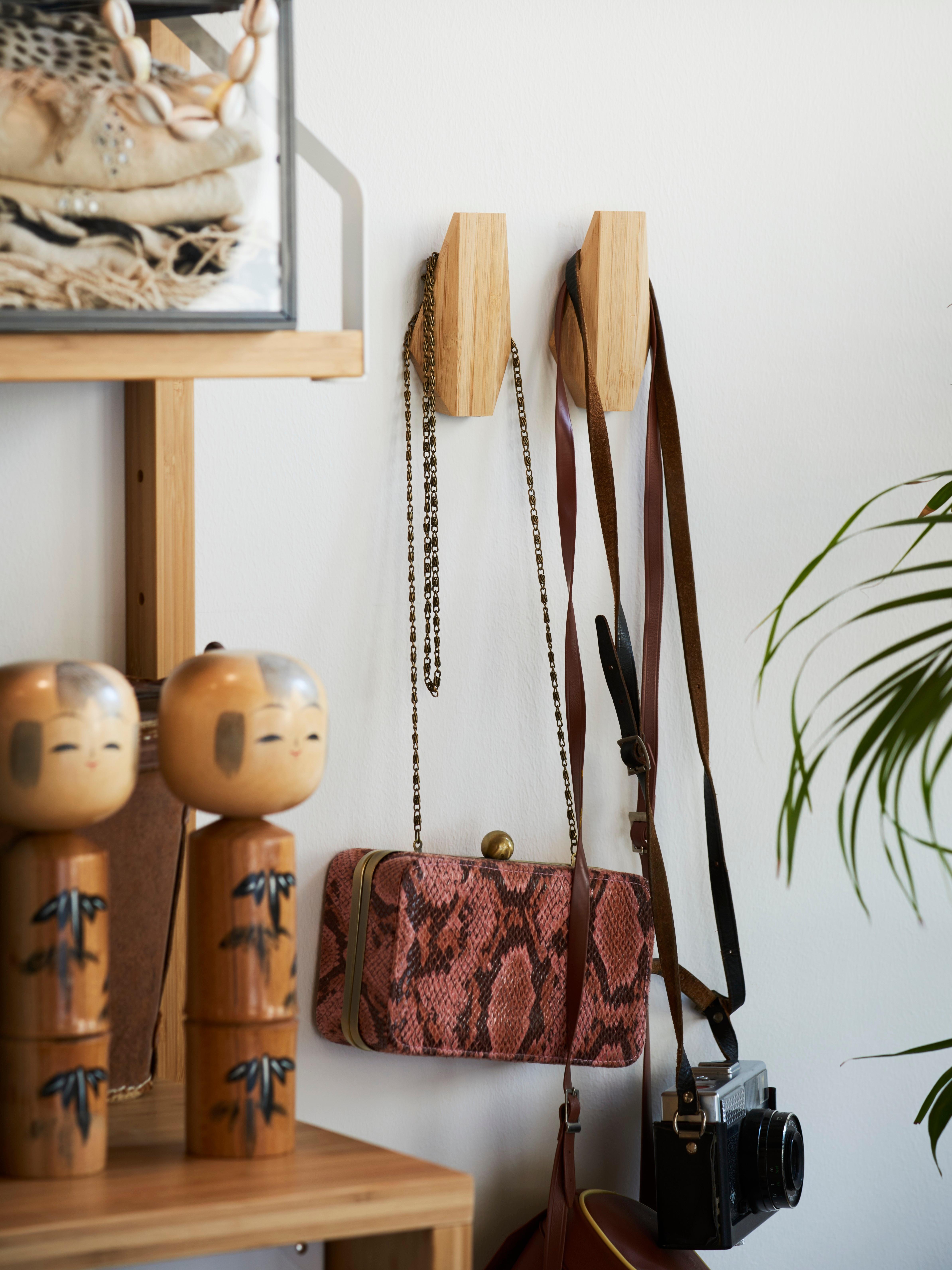 Deux crochets SKUGGIS en bambou, de style géométrique, portant un sac à main et un appareil photo sur un mur à côté d'une étagère en bambou.