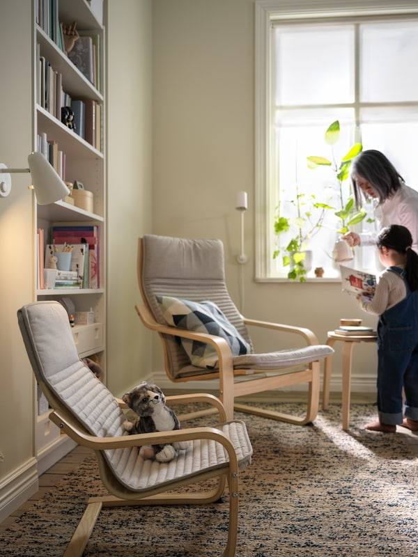 A living room corner with a girl and a woman standing by a pair of light-beige POÄNG armchairs, one of them child-sized.