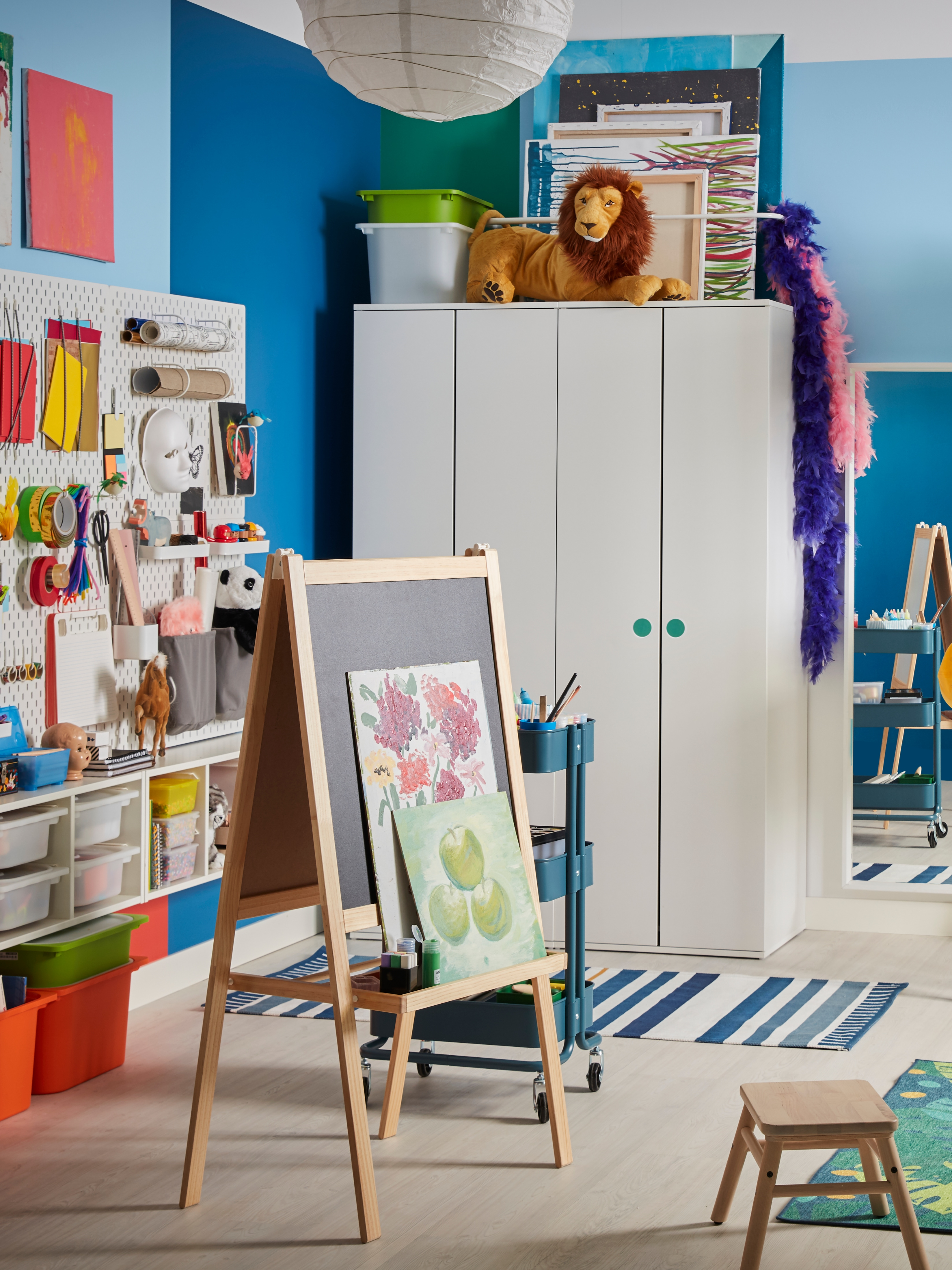 A children's room with two side-by-side white GODISHUS wardrobes and an easel by a pegboard wall of arts and crafts supplies.
