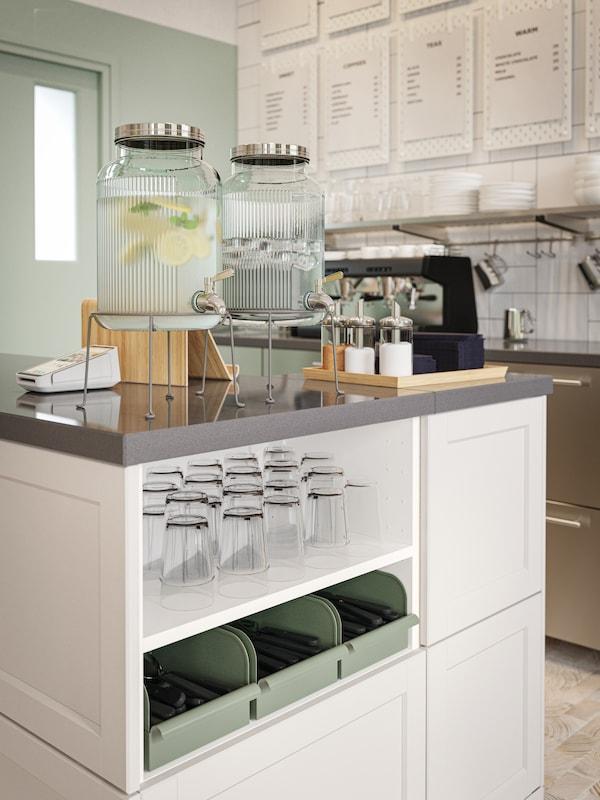 Area self-service vicino al bancone, con due caraffe d'acqua, bicchieri, posate in contenitori metallici grigio-verdi e terminale POS.