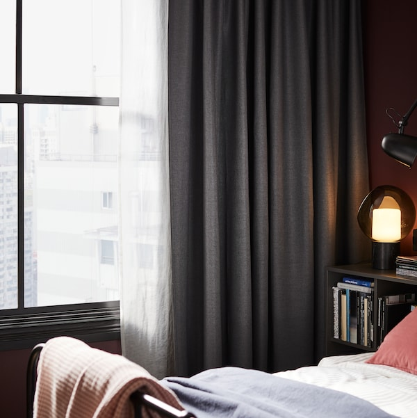 A window by a bed with dark grey ANNAKAJSA curtains and white HILJA curtains on it. There is a lamp on a table by the bed.