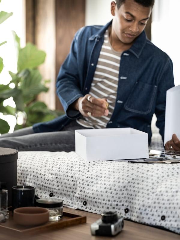 une femme assise sur son lit en train de ranger des objets dans une boîte