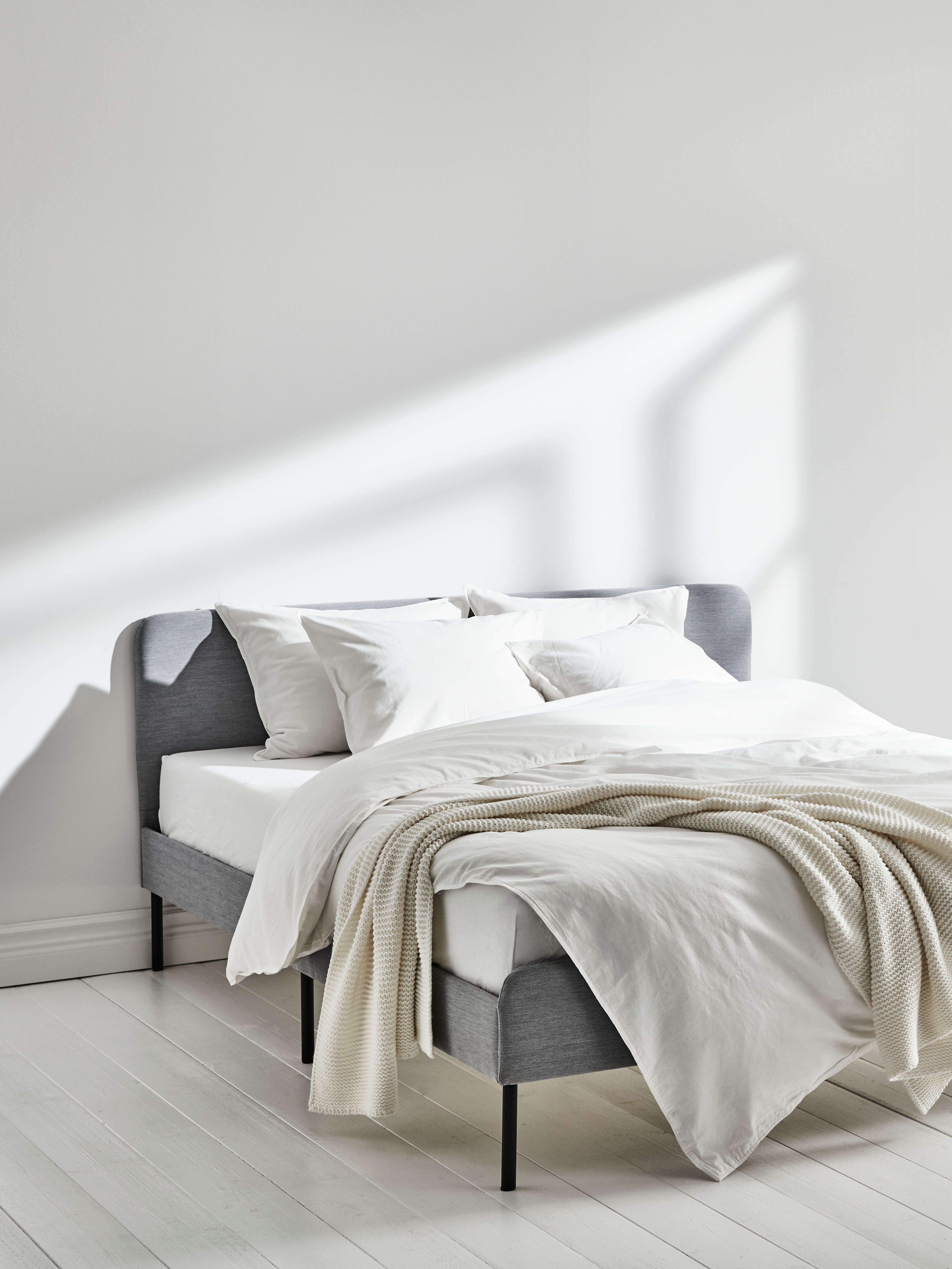 Bedroom with white wall, upholstered bed frame with white mattress, multiple pillows with quilt covers, and throw.