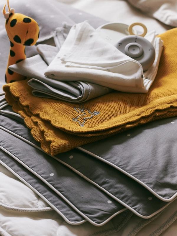 Dětská chůvička UNDVIKA na hromadě textilních výrobků včetně tmavě žluté přikrývky SOLGUL.