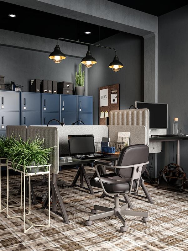 Spazio di lavoro diviso da paraventi in feltro, sedia riunioni in pelle, PC portatile nero, tre lampade a sospensione nere e una pianta.