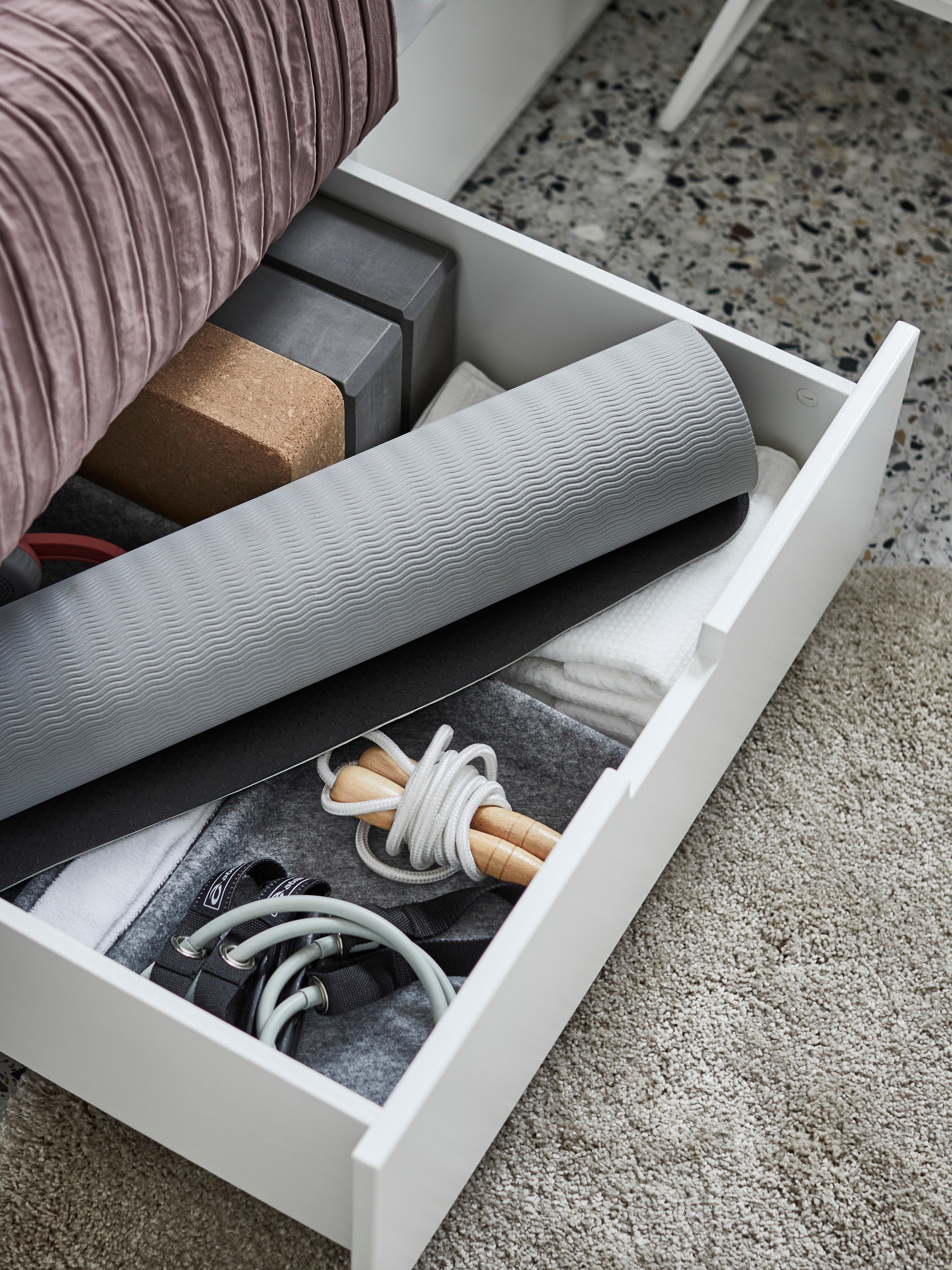 Otvorena ladica s prostirkom za jogu i drugim priborom za vježbanje u NORDLI okviru kreveta s odlaganjem, na sivom tepihu.