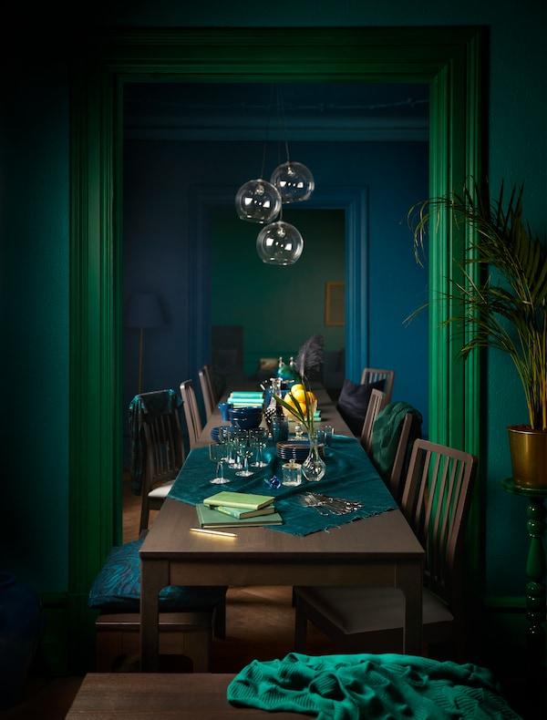 Pièce en palettes vertes et bleues avec une table extensible et des chaises autour. Les lampes suspendues apportent la lumière directement sur la table.