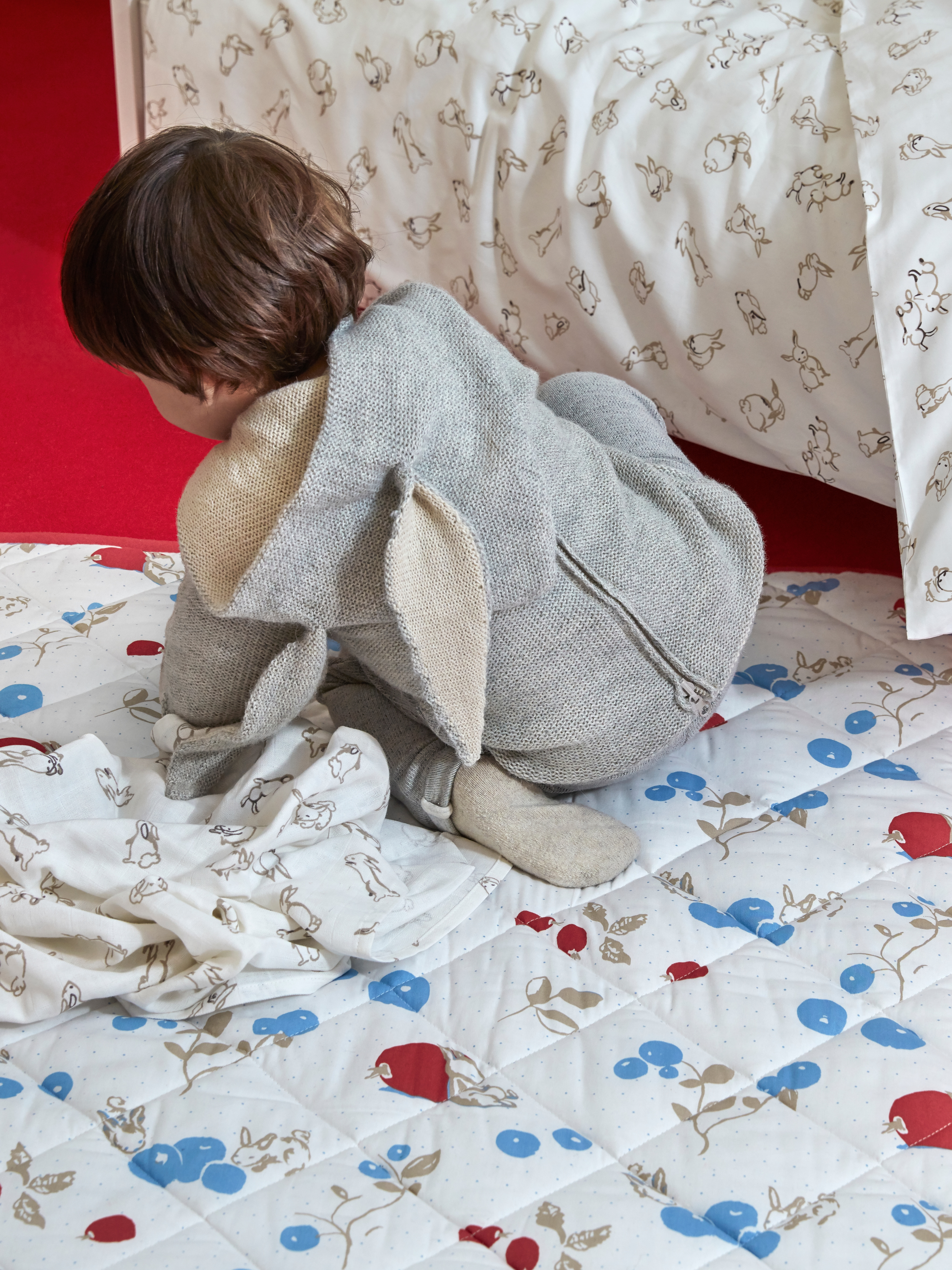 A young child in a rabbit suit, playing on a white and red RÖDHAKE quilt blanket with a rabbits and blueberries design.