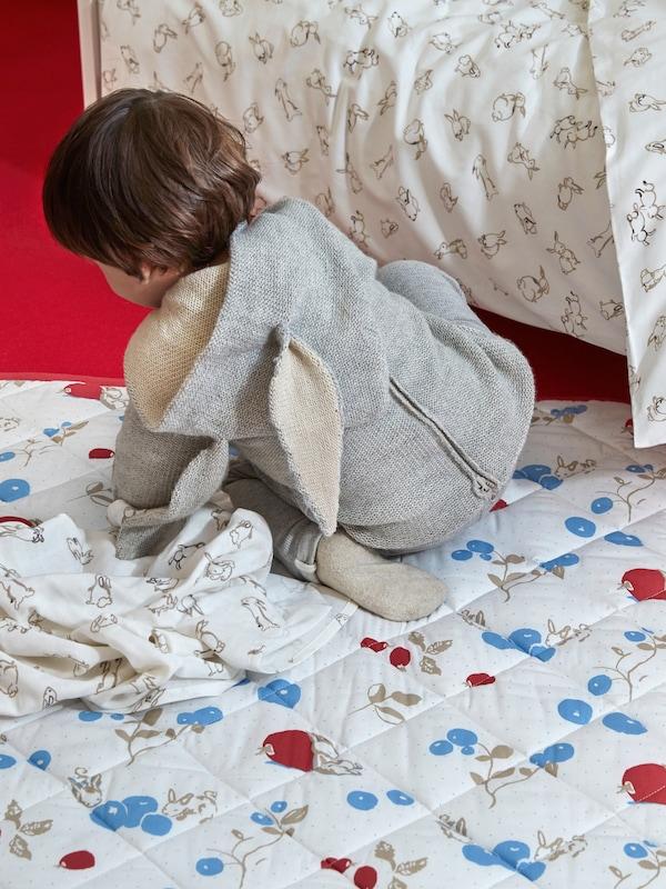 Un niño pequeño con un mono de conejo gateando sobre una manta acolchada RÖDHAKE, junto a un cuna con ropa de cama RÖDHAKE.
