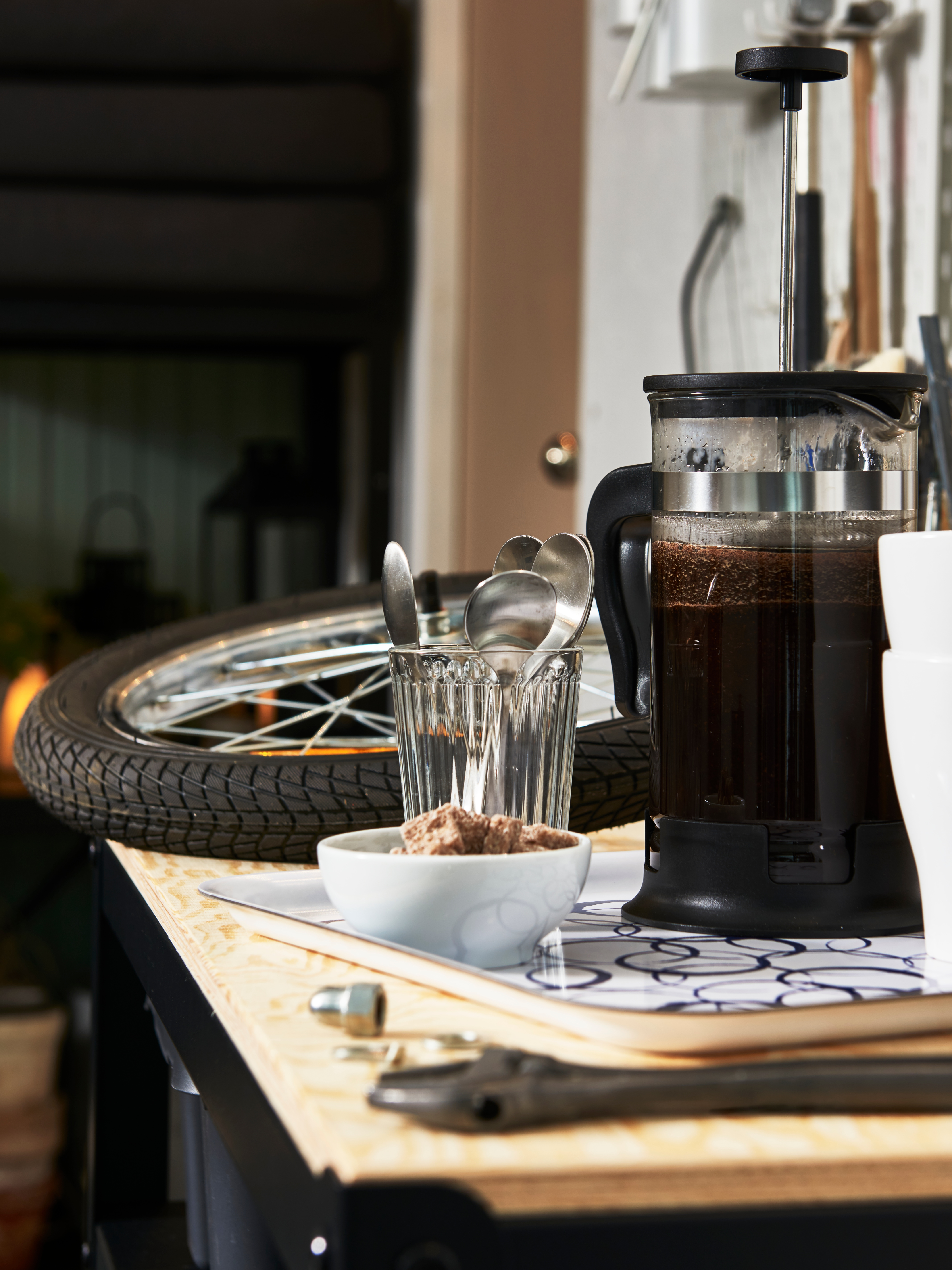 A white MEDLEM tray with a blue circular pattern holds a coffee maker and two mugs by tools and a tyre on a garage worktop.