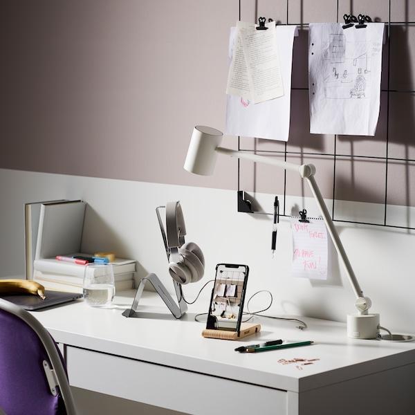 Valkoinen MICKE-työpöytä, jonka päällä on BERGENES-kännykkäpidike, MÖJLIGHET-kuuloketeline sekä työvalaisin. Seinällä pöydän yläpuolella on SÖSDALA-muistitaulu.