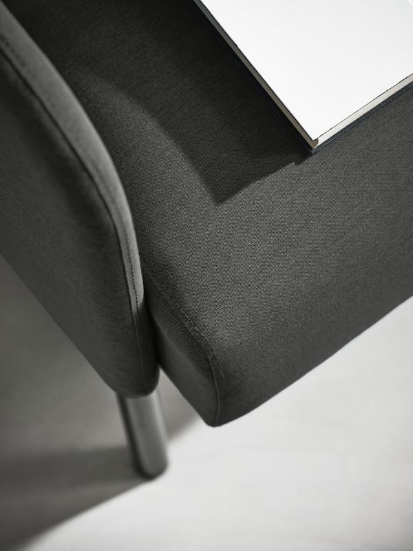 Tempat letak tangan dan tempat duduk sofa dua tempat duduk GLOSTAD berwarna biru dengan cahaya matahari dipantulkan di atasnya dan bahagian atas buku berwarna kelabu.